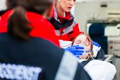 pic of stretcher  - Emergency doctor and nurse or ambulance team transporting accident victim on stretcher - JPG