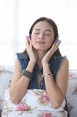 Young Woman Listening Music Through Headphones, Eyes Closed.