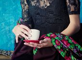closeup of hands of woman holding a cup of coffee against blue painted grunge wall, wearing black la