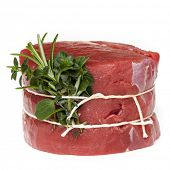 Raw beef steak tied with fresh herbs, isolated on white.