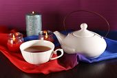 Composition with tea in cup and teapot and candles on table, on color background