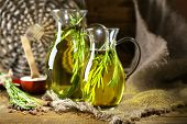 Essential Oil with rosemary in glass jugs, on wooden background