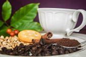 Coffee cup, beans, cinnamon and cracker