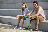 young couple of skateboarders, sitting on concrete steps, talking  on the beach, on a beautiful summer day.