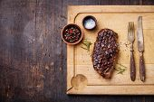 stock photo of darkness  - Grilled New York Striploin Steak with salt and pepper on meat cutting board on dark wooden background - JPG