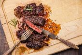 Grilled Ribeye Steak With With Knife And Fork On Meat Cutting Board On Wooden Background