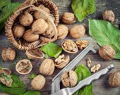 image of nutcracker  - Walnuts nutcracker and basket on old wooden table top view - JPG