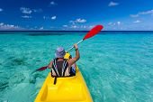stock photo of canoe boat man  - Caucasian man is kayaking in sea at Maldives - JPG