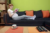 Pregnant Woman On Sofa Reading A Book