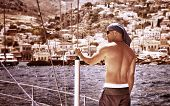 Sexy shirtless man traveling on sailboat along Greek islands, active lifestyle, enjoying leisure time on the sea, summer vacation concept