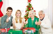 Couple and senior people holding thumbs up at christmas with gifts