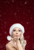 Beautiful woman in Christmas cap blows kiss, isolated on purple