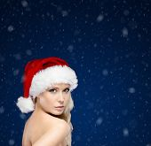 Pretty woman in Christmas cap,snowfall background