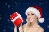 Beautiful woman in Christmas cap hands present, snowy background
