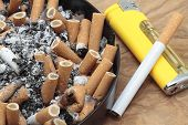 picture of cigarette lighter  - lighter and ashtray full of cigarettes and ash - JPG
