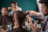 picture of hair cutting  - hairdresser  cuts    hair  with hair clipper on back of the head of handsome satisfied  client in  professional  hairdressing salon - JPG