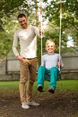 family, happiness, generation, home and people concept - happy father and son swinging on teeterboard outdoors