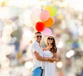 love, wedding, summer, dating and people concept - smiling couple wearing sunglasses with balloons hugging over lights background