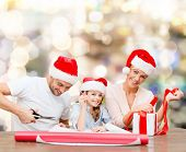 christmas, holidays, family and people concept - happy mother, father and little girl in santa helper hats with gift box and scissors over lights background