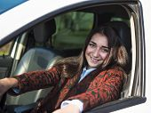Young Pretty Smiling Girl Sitting Behind The Wheel Of A Car