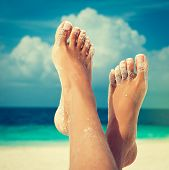 Tanned feet with pedicure with white Sands and the turquoise sea