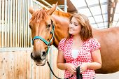 Woman leading pony in horse stable