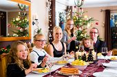 Family of Mother, father, children celebrating Christmas eve with traditional dinner Wiener sausages and potato salad