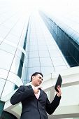 Asian businessman checking outside mails on tablet computer in front of tower building