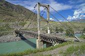 Old Suspension Bridge Across Mountain River, Altai, Russia.