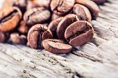 Coffee beans on grunge wooden background.