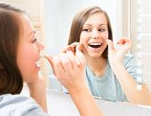 stock photo of teeth  - Beauty young woman flossing her teeth at home - JPG