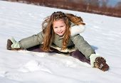 Happy child sit down in the snow