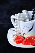 A coffe cup, black and white beads and red marmalade.