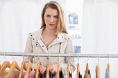 Pretty blonde looking at camera by clothes rail in the store