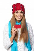 Female in winter hat and scarf showing blank credit card