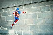 Hopping boy in superhero costume