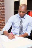 Young businessman writing document at office desk