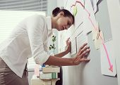 stock photo of bent over  - Female office worker bent over with head lening to a wall and negative business chart - JPG