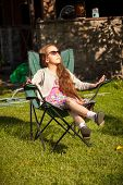 Young Girl Relaxing In Armchair On Grass At Sunny Day