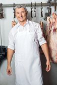 Portrait of happy mature male butcher standing against meat hanging in butchery
