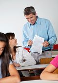 Happy male professor showing paper to student at desk during examination in classroom