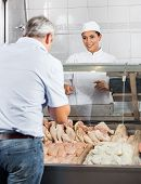 Happy female butcher selling chicken meat to male customer in butchery