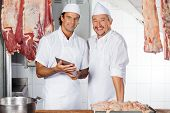 Portrait of happy butchers with digital tablet at counter in butchery