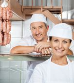 Portrait of happy mature male butcher with female colleague at butchery