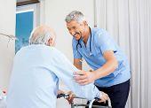Smiling male caretaker helping senior man to use walking frame in bedroom at nursing home