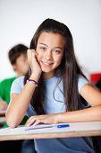 Portrait of happy teenage schoolgirl sitting at desk in classroom