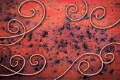 picture of scrollwork  - old rusty metal with peeling red paint and abstract curls and scrollwork on top - JPG