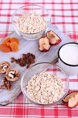 Oatmeal in bowls, mug of yogurt, marmalade, chocolate, raisins, dried apricots and walnuts on wooden cutting board on checkered fabric background