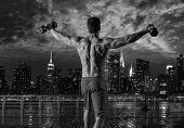 gym man rising hex dumbbells in New York city skyline at night rear view photo mount