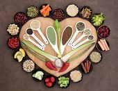 Large healthy heart superfood selection in wooden bowls and measuring spoons over brown paper background.